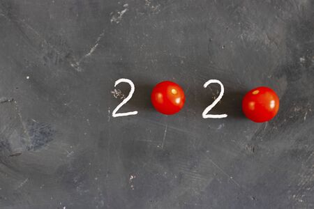 Figures 2020 made with white drown 2 and Two fresh raw tomatoes instead of zero symbol on chalk board black background. Top view. Horizontal with copy space. Minimal Christmas concept Archivio Fotografico