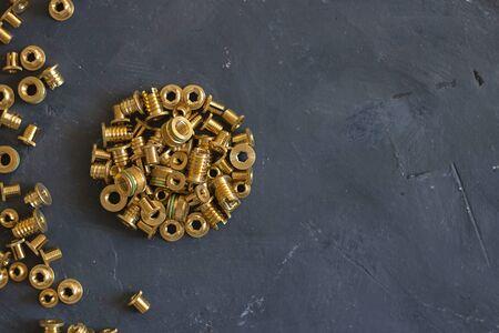 Runde Form aus goldfarbenen Nietmuttern und Lochnuten auf schwarz strukturierter Kreidetafeloberfläche. Nahaufnahme. Horizontal mit Kopienraum. Ansicht von oben. Befestigungselemente, Schrauben und Details.