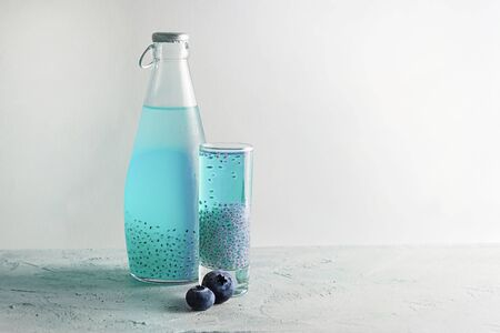 One Shot and bottle with blue basil seeds drink with two fresh blueberries on grey textured background. Horizontal, copy space. Minimal concept about healthy beverage, super food. Falooda, sabja