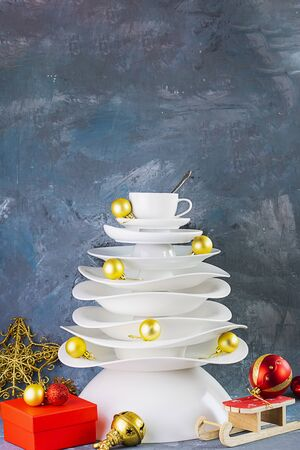 Ceramic white dishes Christmas tree with yellow gold Xmas balls and decoration on dark background. Creative concept, postcard about food, restaurant, menu, party, dishware. Vertical.