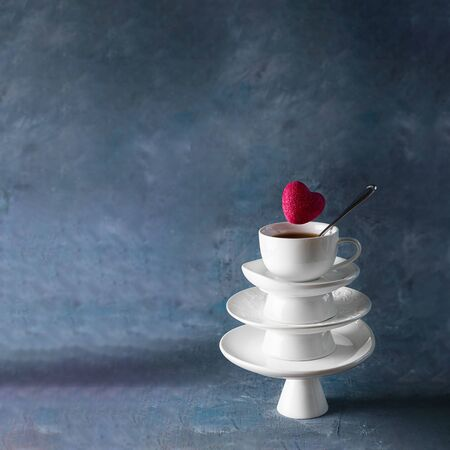 White saucer pyramid with cup of tea on top and flying red hearts candy over it. Creative concept, love, relations, gift, celebrate, restaurant, food levitation, St. Valentine's day. Dark background.