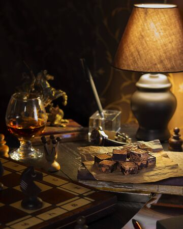 Moody brown composition of desk at man personal area at home with dark chocolate, glass of cognac, chess and lamp on it. Vertical wallpaper about relax time, hobby and food for gentlemen. Monochrome Stockfoto