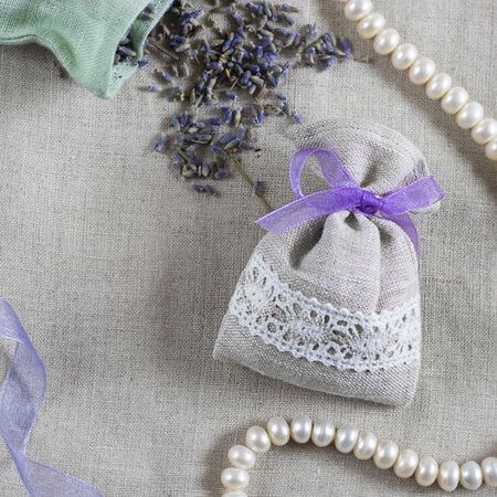 Small linen sack filled with dried lavender decorated with lacework and violet ribbon, two sachets, one is opened and pearl necklace. Top view on thenatural flaxen background. Square