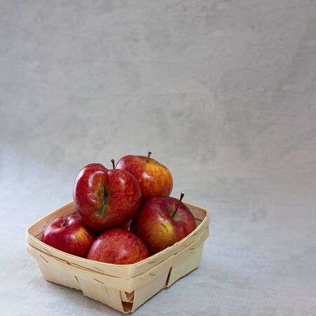 Red fresh organic apples in small wooden pottle with ugly fruit on top. On grey cement background with copy space. Buying imperfect product to reduce waste. Sustainable consumption. Square. Eco trend.
