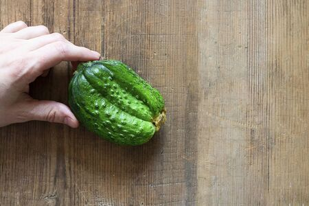 Human Hand holding ugly triple green organic cucumber. Vegetable with unusual shape on brown wooden background with copy space. Buying imperfect product to reduce food waste. Eco trend. Horizontal. Stock fotó