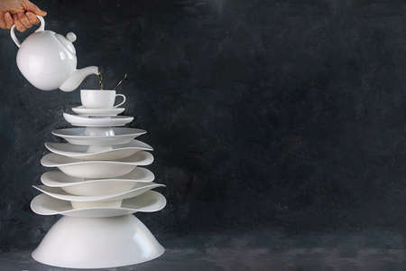 ceramic dishes Christmas tree with cup on top and teapot pouring tea over it, copy space Creative concept about dishware, kitchen, restaurant, cafe, postcard, manufacture plate, tableware Horizontal
