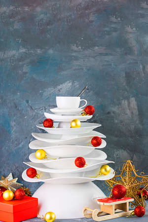 Ceramic white dishes Christmas tree with yellow and red Xmas balls, gift box under on dark background. Creative concept, postcard about food, restaurant, menu, party, dishware. Vertical. Stock fotó