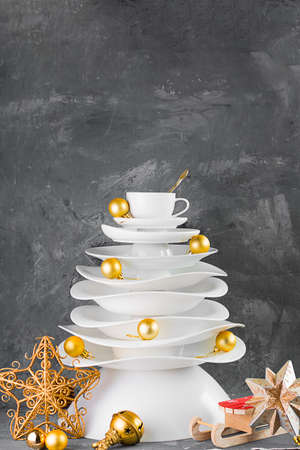 Ceramic white dishes Christmas tree with yellow gold Xmas balls and decoration on dark background. Creative concept, postcard about food, restaurant, menu, party, dishware. Vertical. Stock fotó