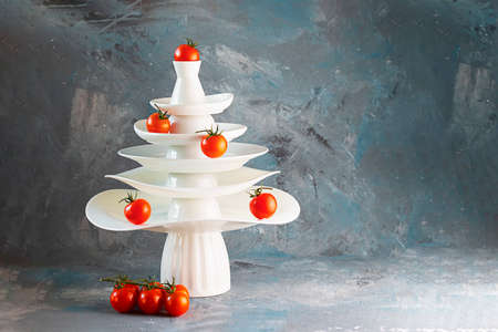 White dishes Pyramid of Christmas tree shape decorated with red tomatoes and bunch below on dark Creative concept, dishware, veg, agriculture, vegetable, kitchen, restaurant, postcard, Xmas, New Year Stock fotó