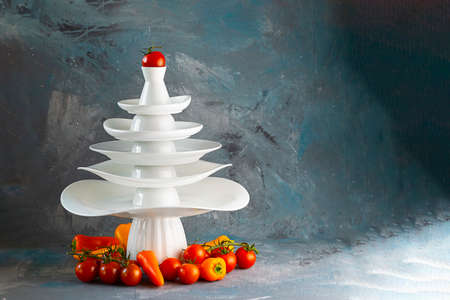 White dishes Pyramid of Christmas tree shape with red tomato on top, vegetables below on dark. Creative concept, dishware, veg, agriculture, kitchen, restaurant, postcard, Xmas, New Year, healthy food