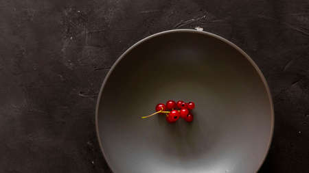 Red currant bunch in empty bowl on textured chalkboard background with copy space. Dark Moody picture. Minimalism about organic berries, contrast, fresh food and ingredien for desserts