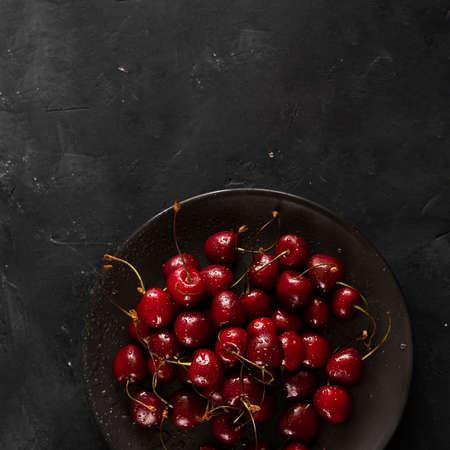Many ripe bright Cherry berries with water drops on black plate on dark chalkboard background. Square shot with copy space. Fresh sweet ingredient for desserts, tarts and pies. Organic agriculture.