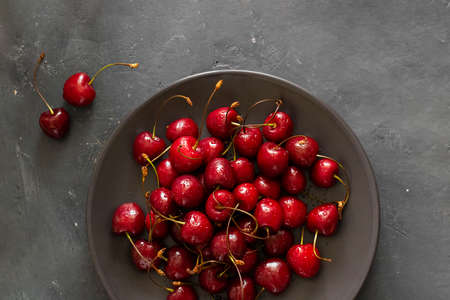 Many ripe bright Cherry with water drops on brown bowl and two berries next to it on dark chalkboard background. Fresh sweet ingredient for desserts, tarts and pies. Organic agriculture. Horizontal.