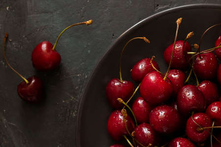 Closeup on many ripe bright Cherries with water drops in brown bowl and two berries next to it on dark chalkboard background. Fresh sweet ingredient for desserts, tarts, pies. Organic food. Horizontal