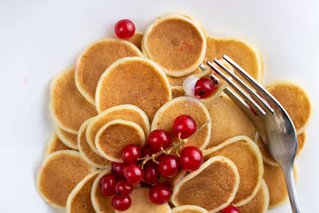 Closeup of tiny pancake cereal on white plate served with red currant berries and fork. Trendy breakfast, small round baked crepe batter drops. Horizontal. Homemade food. Stock fotó