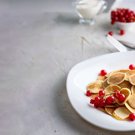 Tiny pancake cereal on white plate served with red currant berries and ingredients on grey cement table. Trendy breakfast, small round baked crepe batter drops. Homemade food. Square with copy space