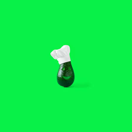 Finny green fresh avocado, with smile and eyes on face wearing clean white restaurant Chefs hat on green chroma key background. Square with copy space. Creative concept for healthy cooking and food.