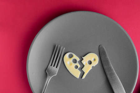 Cheese heart broken in two parts on grey plate with fork and knife on red background. Food concept. Agriculture and dairy manufacture. Top view