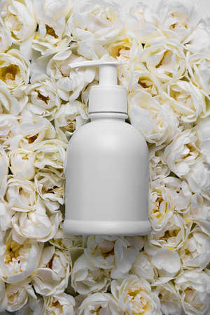 Mockup dispenser bottle on background of Live wall made up with white wild roses. Top view. Full bloom, monochrome flora design. Trendy flower carpet. Cosmetics or sanitizer with aroma. Vertical. Stock fotó