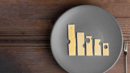 Lowering trend made with cheese graphs on grey plate with fork next to it on wooden table with copy space.