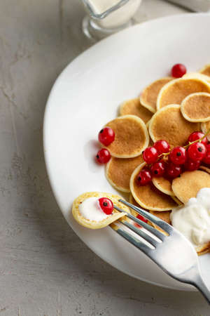 Tiny pancake cereal on white plate served with red currant berries and ingredients on grey cement table. Trendy breakfast, small round baked crepe batter drops. Homemade food. Vertical Stock fotó