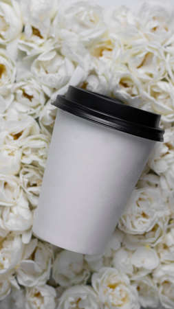 Mockup paper coffee cup on background of Live wall made up with white wild roses. Top view. Full bloom, monochrome flora design. Trendy flower carpet. Hot drink take away. Vertical banner