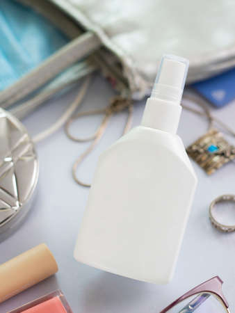 Mockup white bottle of hand sanitizer surrounded with things from woman purse. Vertical shot about health care, hand hygiene and Protection Coronavirus, Covid-19. Lady bag content. Spray anticeptic. Stock fotó