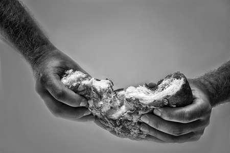 Brot wird in männlichen Händen in zwei Hälften zerrissen Standard-Bild
