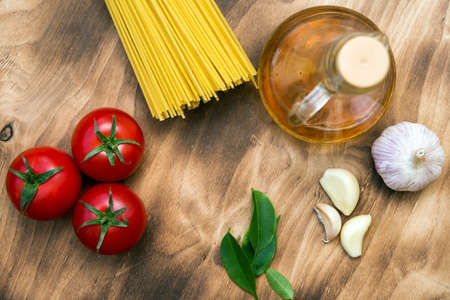 raw spaghetti, fresh tomatoes, garlic, olive oil and herbs are on a wooden table Zdjęcie Seryjne