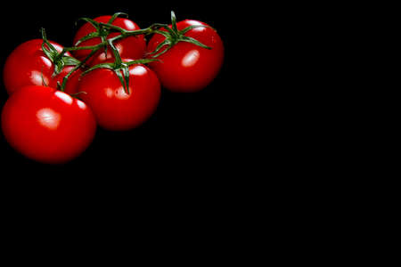 fresh red tomatoes in the left corner black background