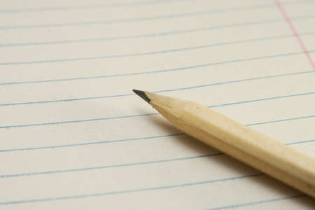One Sharpened Yellow Pencil on a Diagonal with a Paper Background