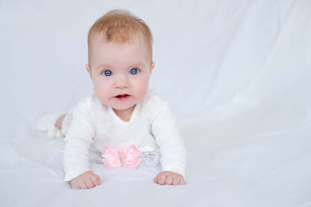Cute baby with blue eyes in white dress with pink bow lying on her stomach looking at camera, white background,