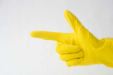 hand in yellow glove, finger gesture forward, direction indication