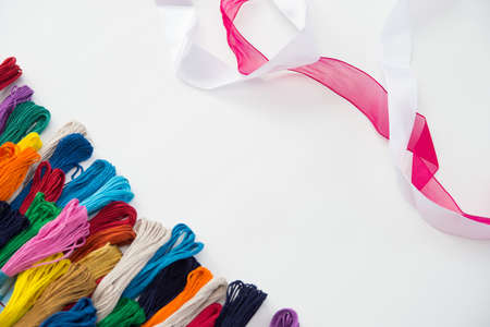 colored embroidery floss and white and red ribbon, top view, white background, Flatley