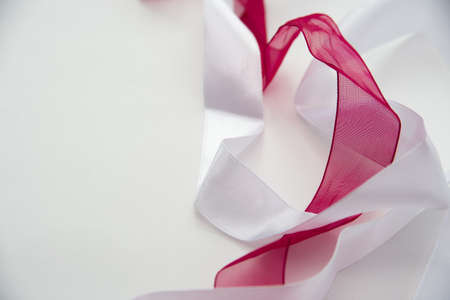 two satin ribbons of red and white, on a white background, close-up, mixed, Фото со стока