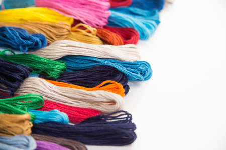 multi-colored thread floss lie on a white background from the bottom up perspective, thread for cross stitch Фото со стока