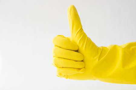 hands in yellow gloves, thumb up, white background, sign that all is well,