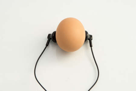 small black headphones lie next to the chicken egg as if the egg is listening to music, white background orange egg