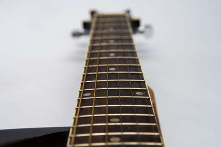 Guitar fretboard close-up top view of the neck of the guitar and strings on white isolated background. Acoustic guitar perspective along fretboard