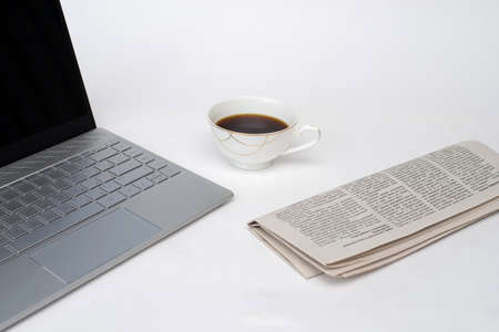 laptop, fresh newspaper and hot coffee on white background, white Desk of office worker, financial consultant Zdjęcie Seryjne