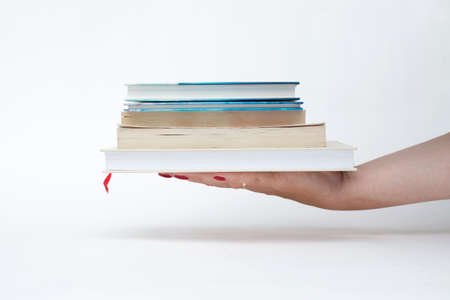 female hand with red manicure holding a stack of books white background