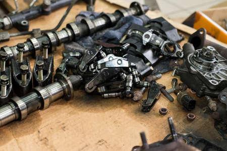 camshaft, bolts, nuts, rocker arm tappet valve taken from a broken car top view
