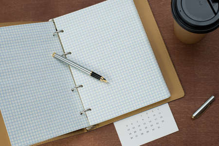 Calendar planner with fountain pen and hot coffee on wood table.office tool. Zdjęcie Seryjne - 129312330
