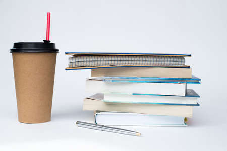 a paper Cup of coffee with a red straw stands next to a stack of books on a white background Zdjęcie Seryjne
