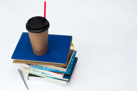 paper Cup for coffee with a red straw stands on a stack of books, white background