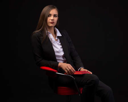 young beautiful businesswoman girl sitting on chair with red notebook on dark background in business clothes, beautiful brunette in jacket