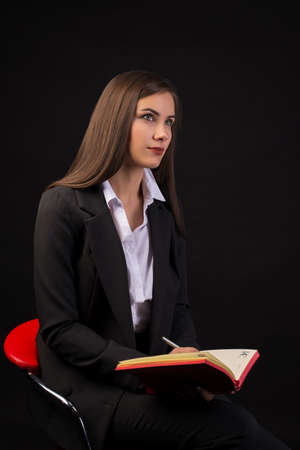 young beautiful businesswoman girl sitting on chair with red notebook on dark background in business clothes, beautiful brunette in jacket Stok Fotoğraf - 133101225