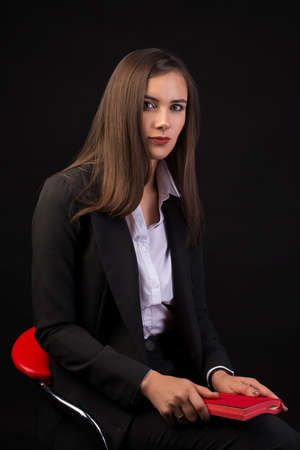 young beautiful girl with long black hair sitting on a red chair and holding a red notebook, black background, business suit girl