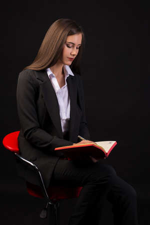 young beautiful girl sitting on red chair with red Notepad in hands black background, business lady, girl in business clothes black background Stok Fotoğraf - 133101229