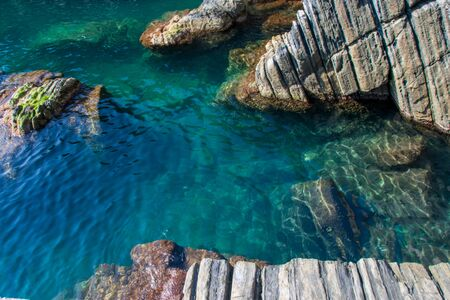 The turquoise water seen among the rocks in the city of Riomaggiore, Cinque Terre, La Spezia, Italy Banco de Imagens